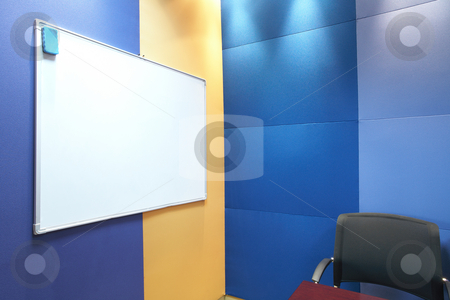 Whiteboard against blue wall stock photo, Whiteboard and a grey office chair against blue and yellow soundproof panels in a modern boardroom by Sean Nel