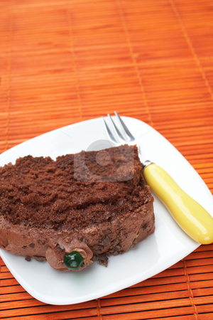 Slice of chocolate cake stock photo, Slice of fresh chocolate cake with a small fork on orange background by Sean Nel
