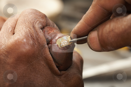 Jeweler making rings stock photo, Goldsmith working on an unfinished 22 carat gold ring with his hard working hands. Half of the Diamonds already embedded. by Sean Nel