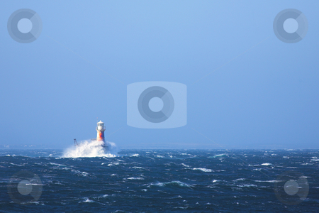 Lighthouse in the sea at Simons Town stock photo, The roman styled lighthouse inside the bay at Simons Town, Western Cape, South Africa. Extremely windy day with choppy water and large waves breaking against the lighthouse. by Sean Nel
