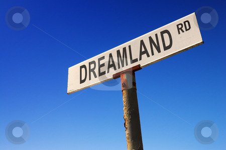Sign against blue sky stock photo, Weathered old road sign against a clear blue sky - Concept image: Road to DREAMLAND by Sean Nel