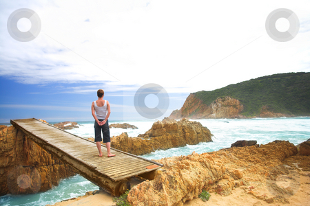 Woman on bridge next to ocean stock photo, Woman facing the sea standing on a bridge next to a wild ocean on a stormy, overcast day at The Heads in Knysna, South Africa by Sean Nel