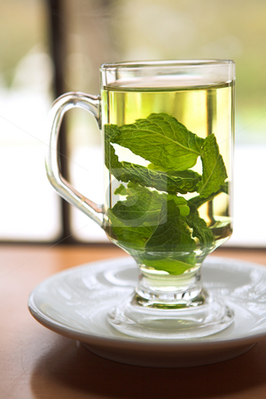 Green mint tea stock photo, Hot green mint tea standing next to a window with whole mint leaves by Sean Nel
