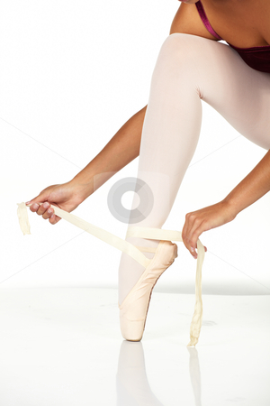Tying ballet shoes stock photo, Young female ballet dancer showing how to tie a ballet Pointe Shoe against a white background. NOT ISOLATED by Sean Nel