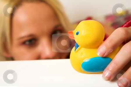 Woman #153 stock photo, Woman playing with a plastic toy duck.  Shallow depth of field, duck and hand in focus, face out of focus. by Sean Nel