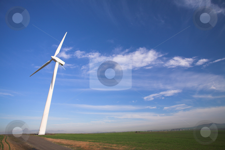 Wind powered electricity generator stock photo, Wind powered electricity generator standing against the blue sky in a green field on the wind farm by Sean Nel