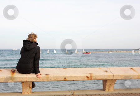 Antibes #65 stock photo, Tourist sitting on a bench overlooking the sea in Antibes, France.  Copy space. by Sean Nel