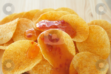 Chips and dip stock photo, Crispy golden brown potato chips with a hot salsa dip sauce on a wooden presentation plate (shallow depth of field) by Sean Nel