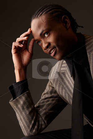Black Businessman stock photo, Black African businessman on a dark background in various positions and with various facial expressions. Part of a series by Sean Nel