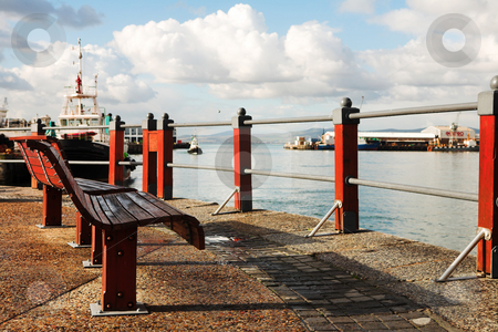 Benches at the harbour stock photo, Two red seats at the Cape Town Waterfront harbour in South Africa, with boats in the background on a cloudy day. by Sean Nel
