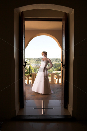 Young blonde bride wearing wedding gown stock photo, Young blonde bride with champagne colored wedding gown and red lips. She is standing outside the doorway on a porch by Sean Nel