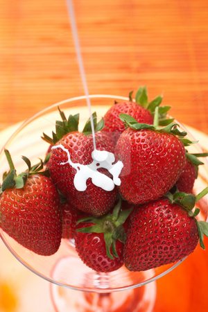 Fresh strawberries in a glass stock photo, Fresh strawberries with stems covered with cream in a glass on orange background by Sean Nel