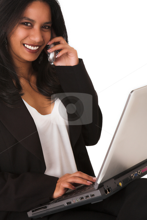 African businesswoman on the phone stock photo, African businesswoman in black dress business suit, sitting down, with notebook computer on her lap and telephone next to her ear. Isolated on white by Sean Nel