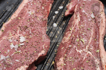 Raw meat stock photo, Raw steaks being prepared in a black cast iron skillet by Sean Nel