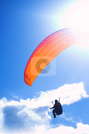 Paraglider silhouetted against a blue sky and clouds stock photo, Paraglider launching from a ridge with an orange canopy and the sun from behind. The paraglider is a silhouette and the shot is taken right after takeoff. The paraglider unfocused with movement, with the main focus on the canopy by Sean Nel