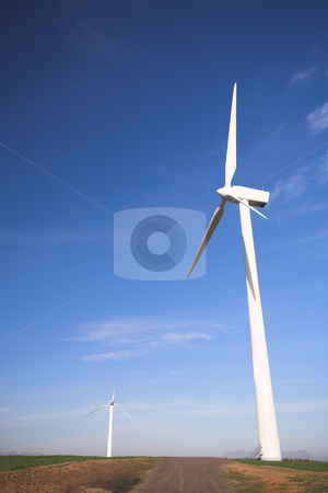 Wind powered electricity generators stock photo, Wind powered electricity generators standing against the blue sky in a green field on the wind farm by Sean Nel