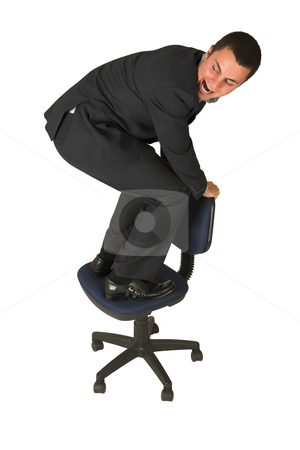 Businessman #234 stock photo, Businessman wearing a suit and a grey shirt.  Making a stunt on an office chair. by Sean Nel