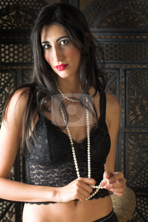 Beautiful young Italian woman in black Lingerie stock photo, Beautiful young sexy adult Italian woman with long black hair, and a string of pearls, in black lace lingerie on a textured wooden background  by Sean Nel