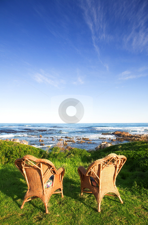 Chairs at the sea stock photo, Wicker cane chairs on a lawn next to the sea  by Sean Nel