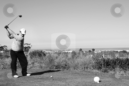 Golfer #59 stock photo, A golfer playing golf on a green.  Movement on golf club, but head is in focus. by Sean Nel