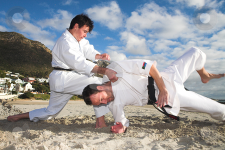 Men practicing Karate on the beach stock photo, Young adult men with black belt practicing fighting on the beach on a sunny day  by Sean Nel