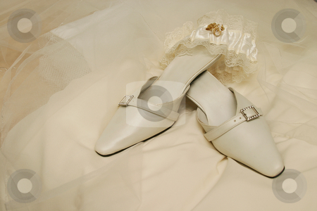 White sandals stock photo, White sandals and garter on wedding dress by Sean Nel