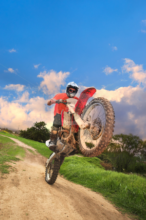 Offroad Bike stock photo, Young man riding around on his dirtbike doing tricks and getting dirty. Movement on edges of motorbike by Sean Nel