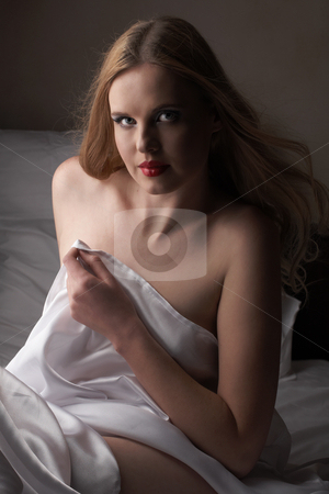 Nude adult woman stock photo, Sensual naked young blonde adult Caucasian woman, wrapped in a satin, silk sheet. High contrast image. by Sean Nel