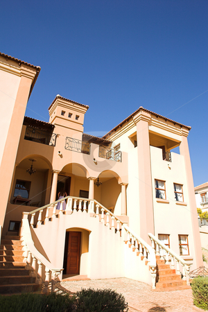 Three storey mansion against a blue sky stock photo, Orange and peach colored three storey mansion against a blue sky on a summer day. Large staircase leads to the front door. by Sean Nel