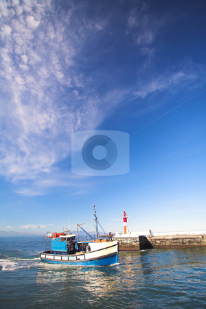 Fishing boat entering harbor entrance  stock photo, A fishing boat entering the harbor at Kalk bay harbor in the Western Cape, South Africa. A sunny summer day, with clear blue skies and calm water and the left harbor entrance (red) lighthouse visible in the background by Sean Nel