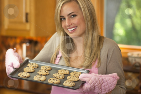 Attractive Blond Woman Baking Chocolate Chip Cookies stock photo, A young woman is holding a baking sheet of cookies and smiling at the camera.  Horizontally framed shot. by Edward Bock