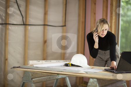 Woman Working at Construction Site stock photo, A young woman is looking at a laptop and talking on the phone.  She is working at a construction site.  Horizontally framed shot. by Edward Bock