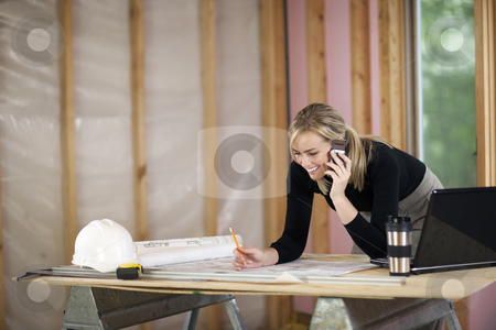 Woman Working at Construction Site stock photo, A young woman is looking at blueprints and talking on the phone.  She is working at a construction site.  Horizontally framed shot. by Edward Bock