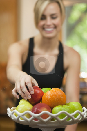 Woman Eating Fruit  stock photo, A young woman is picking up a piece of fruit, smiling, and looking away from the camera.  Vertically framed shot. by Edward Bock