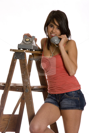 Talking on the phone stock photo, Teenage girl standing on ladder talking on a old rotary phone, looking at the camera by Yann Poirier