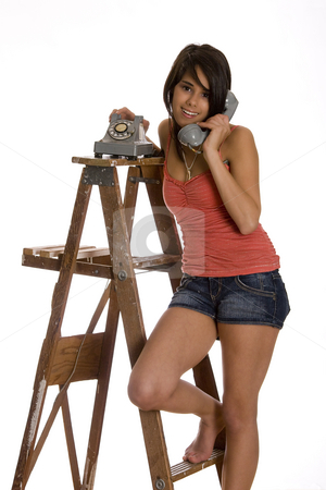 Smilling on the phone stock photo, Teenage girl standing barefoot on ladder talking on a old rotary phone with a great big smile by Yann Poirier