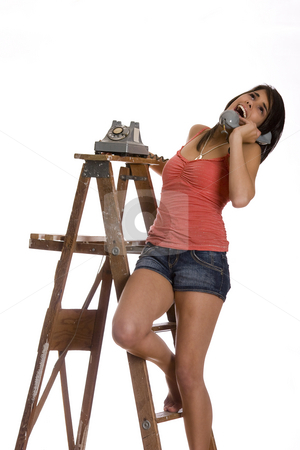 Falling over stock photo, Teenage girl standing barefoot on ladder talking on a old rotary phone with and falling over laughing by Yann Poirier