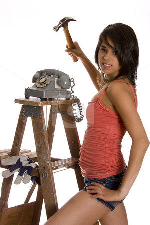 About the smash stock photo, Teenage girl standing on ladder about to smash old rotary phone with a hammer by Yann Poirier