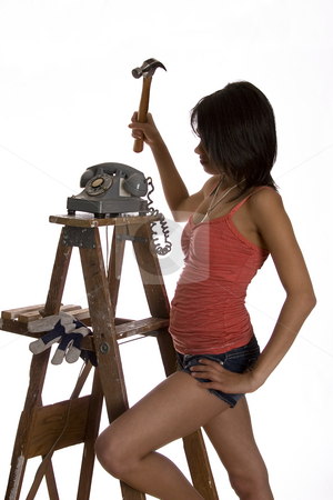 Smashing phone stock photo, Teenage girl standing on ladder about to smash old rotary phone with a hammer by Yann Poirier