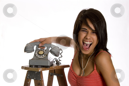 Screaming mad stock photo, Screaming mad teenage girl standing on ladder slamming an old rotary phone by Yann Poirier