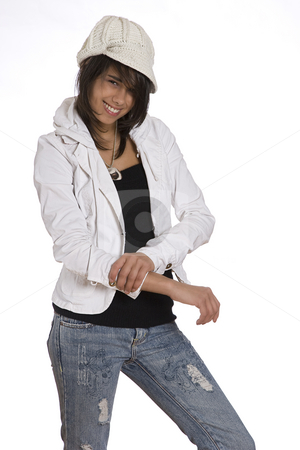Pulling sleeve up stock photo, Teenage girl pulling up her sleeve wearing knitted hat and jeans with holes and a great big smile by Yann Poirier
