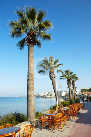 Outdoor Cafe stock photo, Empty wicker tables and chairs at an outdoor cafe with Tall palm tree against a clear blue sky and the Aegean in the background on a sunny day by Sean Nel