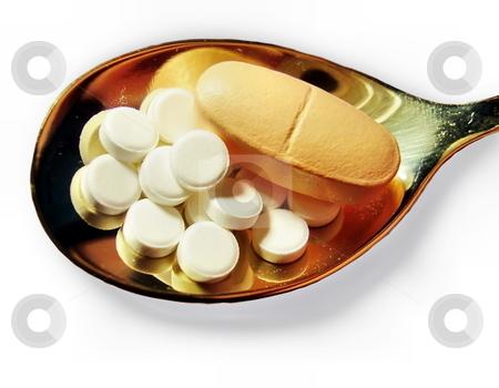 Pills on a teaspoon stock photo, Pills on a teaspoon by Sergey Gorodenskiy