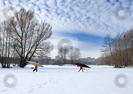 In search of water. stock photo, Two oarsmen with oars and kayaks go on ice of the frozen lake. by Vladimir Blinov