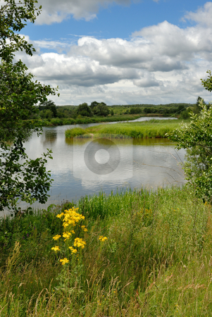 Landscape with the river and clouds. stock photo, The river with island, a grass on coast, clouds in the sky and their reflexion in water. by Vladimir Blinov