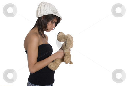 Sad teen girl stock photo, Teenage girl wearing a black tube top, knitted hat and jeans with holes holding a brown stuff dog plush toy with sad expression by Yann Poirier