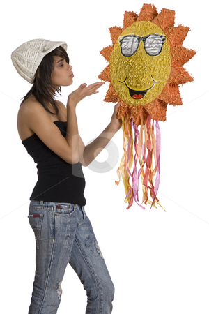 Kissing the sun stock photo, Teenage girl wearing a black tube top, knitted hat and jeans with holes holding a sunny pinata by Yann Poirier