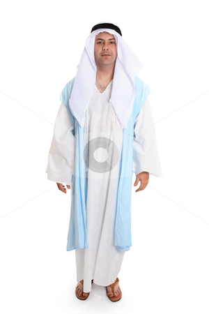 Biblical man stock photo, Man in ancient clothing reminiscent that worn of biblical times. He is wearing a robe (thobe) and cloak, headdress and leather sandals   Variations are still worn today. by Leah-Anne Thompson