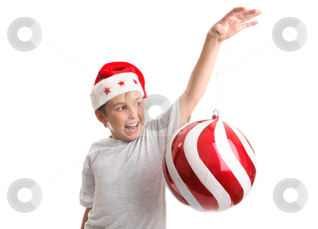 Boy with an oversized Chirstmas Bauble stock photo, A enchanted child holding an oversized red and white swirled Christmas decoration in his hand. by Leah-Anne Thompson