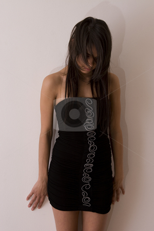 Depress teen stock photo, Teenager girl in little black dress against a wall holding her head down by Yann Poirier